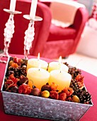 Advent arrangement of four white pillar candles in metal box