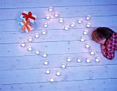 A child lying on floorboard beside tealights arranged in a star shape with presents next to it