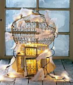 Antique bird cage decorated with pillar candles, fairy lights and white feathers