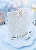 A white menu card on a Christmasy plate