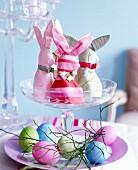 Selbstgenähte Eierwärmer in Hasenform & bunt gefärbte Eier auf Glasetagere