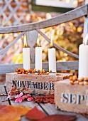 Kerzenständer aus Backstein mit drei weißen Kerzen herbstlich dekoriert mit Blättern & Beeren