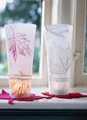 Close-up of two leaf-patterned hand-crafted candle lanterns on windowsill