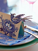 Place card with bird motif on plate