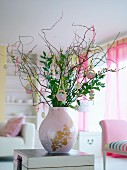 Twigs decorated for Easter in a pink vase