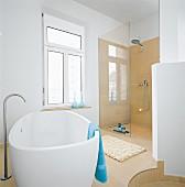 A modern bathroom with a white bathtub and a glazed shower area