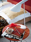 A note book and a lamp on an ethnic-style bedside table