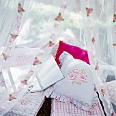A romantic seating area with cushions under a mosquito net