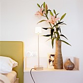 A vase of lilies and a modern table lamp on a wall shelf next to a bed