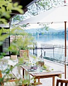 A table laid on a terrace overlooking the Wörthersee