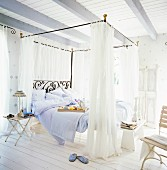 A romantic, country-style bedroom in white with a metal four poster bed