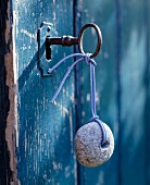 Key with stone pendant with hole in the middle inserted into door