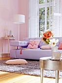 Lilac sofa and silver-leaf side table in living room with pink walls