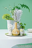Variety of twigs and flowers in vases on tray on table