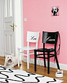 One black and one white chair with names on backs against pink wallpaper