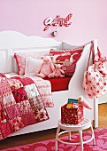 White, wooden, child's bed with scatter cushions and patchwork blankets in shades of red against pink wall