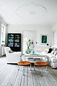 White living room with black cabinet, loose-covered armchair and leather stools