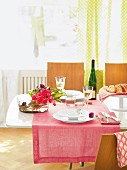 Dining table with pink table cloth, flowers in bowl and white wine