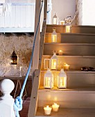 Burning candles and lanterns on a flight of wooden stairs