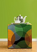 Teapot and teacup on multicoloured, retro-style pouffe against green wall