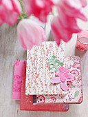 Several pink and red notebooks in floral covers