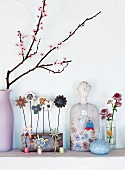 A flowering spring twig in a vase next to decorative objects