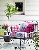 Wrought iron chair with floral cushions on wooden veranda