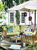 Wooden sofa set with green seat cushions and colourful scatter cushions under parasol on deck