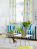 Blue and white striped sofa and curtains with leaf pattern in living room