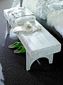 Rustic wooden bench beside bed with towel, socks and handkerchief