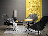 And elegant lounge area in grey and yellow – wicker chairs around a small round table with a golden yellow silk hanging in the background