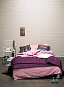 Cosy double bed with purple blanket and pink pillows against whitewashed brick