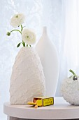 White buttercups in a vase with a white knitted cover