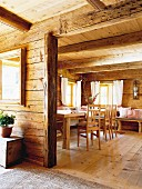 View into rustic interior with dining table and wood-beamed ceiling