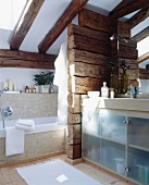 Bathroom with sloping ceiling and partition of wooden beams