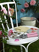 Secateurs and gardening gloves on a chair in a garden next to a rose bush