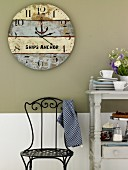 A large homemade clock made from weathered wooden boards hung on a grey kitchen wall