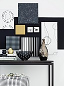 Frames covered in various black and white wallpapers on wall above black console table