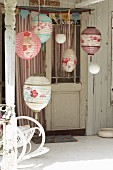 Various painted paper lanterns and a partially visible rocking chair on a terrace