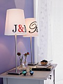 Two table lamps on chest of drawers against lilac wall