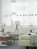 White sofa and coffee table in front of window with panel curtains