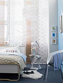 Bed below windows with panel curtains in bedroom with pale blue wall