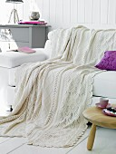 White wool blanket and purple scatter cushion on white leather couch