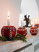 Candles in Christmas apples on a window sill