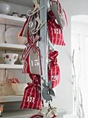 Rot-weiße Säckchen als Adventskalender an Metallkette hängend