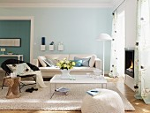 Living room with white furniture and pale blue and turquoise walls
