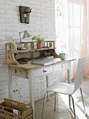 A white, shabby style wooden bureau with a modern chair and a newspaper holder