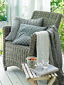 A grey wicker armchair with decorative cushions and blankets in various shades of grey on a summery balcony