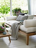 A wooden sofa with upholstered cushions on a summery veranda