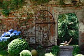 An old garden wall with a wrought iron gate